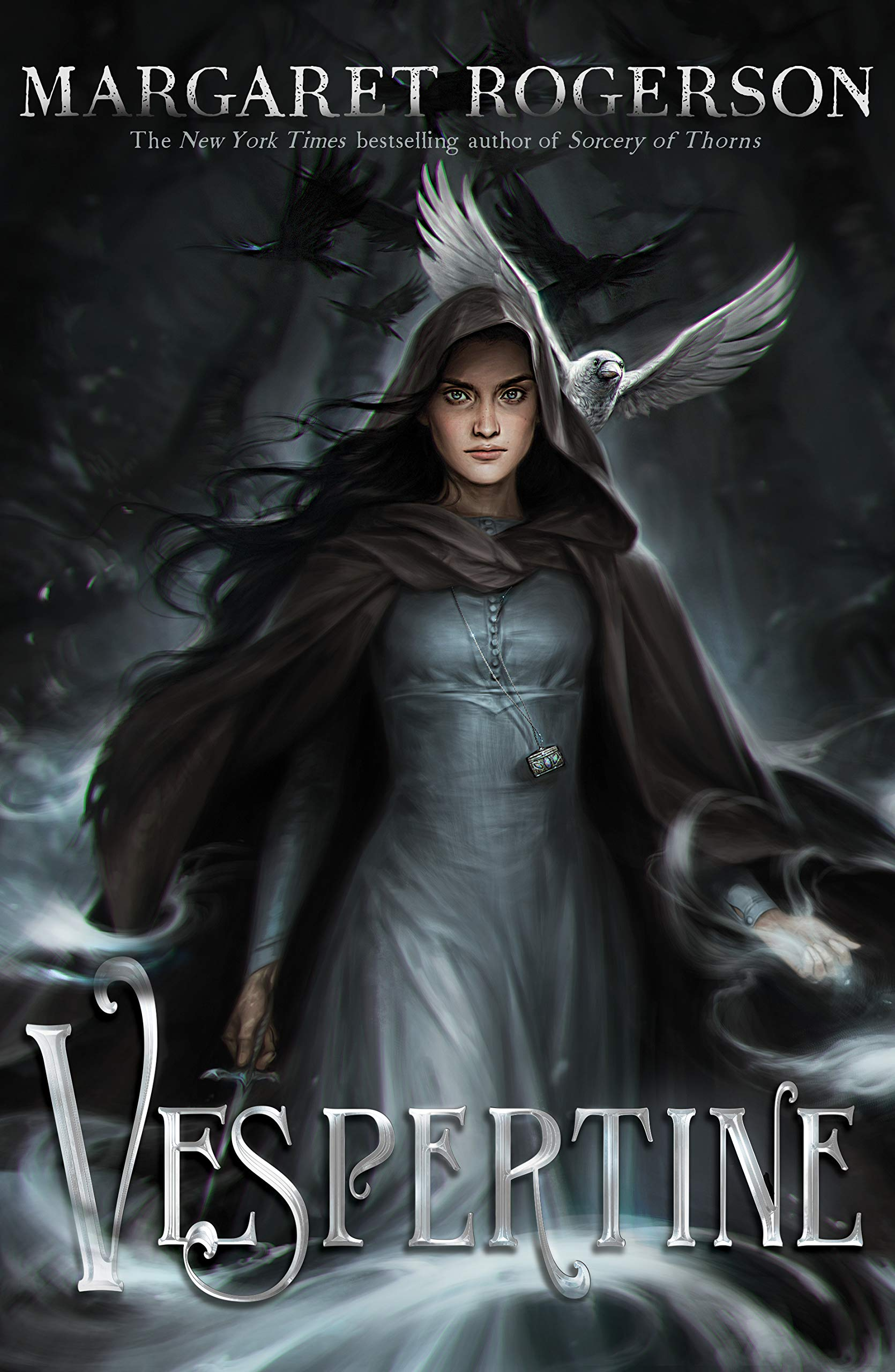 Cover for Vespertine by Margaret Rogerson. It features a white woman facing the reader. The wind blows through her cloak and dark hair while crows fly behind her. The whole thing is dark in tones of black and grey with a single white crow behind the character's left shoulder. The title is on the bottom of the cover in silver letters.